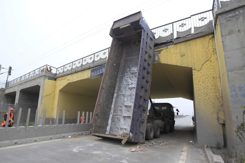 郑州自卸车被卡桥下 司机当场昏迷